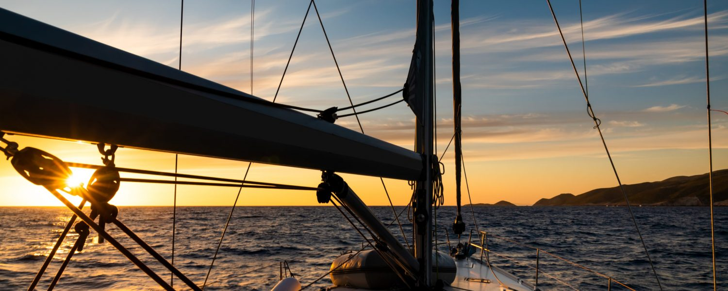 Yacht sailing at sunset during a storm. Luxury vacation at sea.